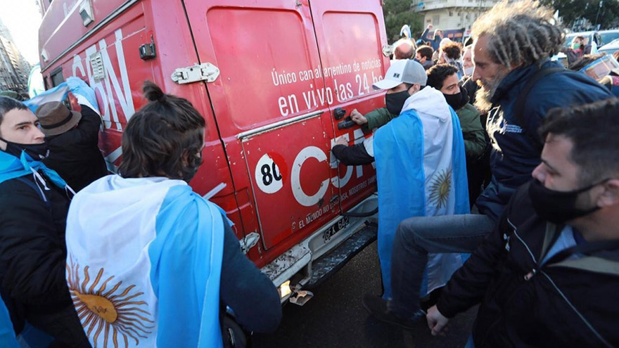 Personas subiertas con banderas cargan contra el móvil de C5N.